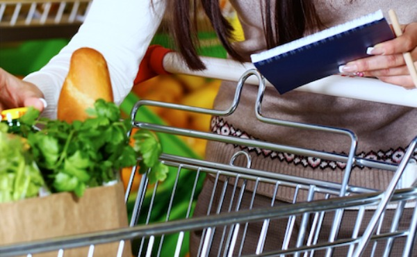 grocery cart with a woman's hands reaching into a grocery bag
